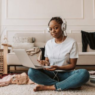 black girl sitting crosslegged using a laptop and wearing headphones