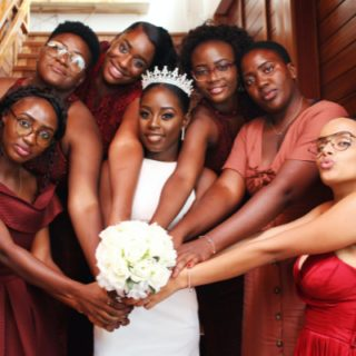 Black bridesmaids in brown dresses surrounding a bride in white holding flowers