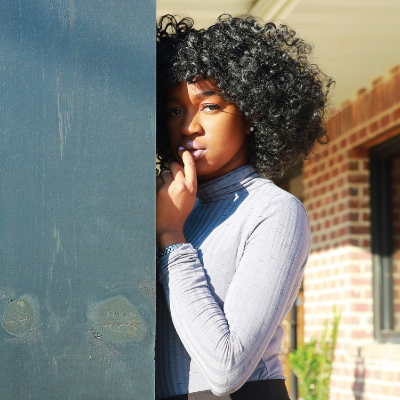 black girl leaning on the wall with curly hair
